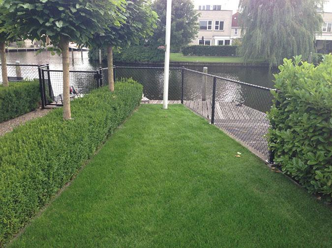 tuinhek tussen gras en steiger